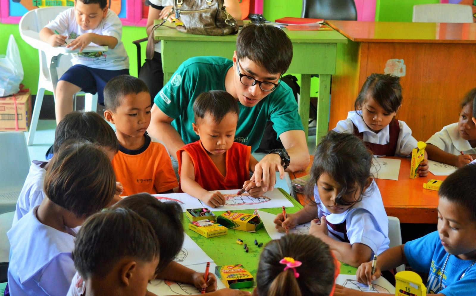 A volunteer in the Philippines helps a child in the classroom as part of his service learning trip abroad